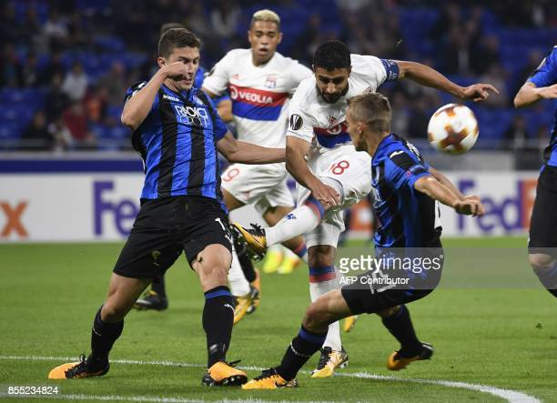 Atalanta's Italian defender Mattia Caldara and Belgian defender Timothy Castagne fight for the ball with Lyon's French midfielder Nabil Fekir during...