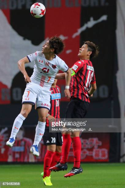 Ataru Esaka of Omiya Ardija and Hiroki Miyazawa of Consadole Sapporo compete for the ball during the JLeague J1 match between Consadole Sapporo and...