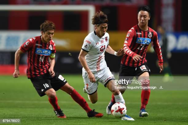 Ataru Esaka of Omiya Ardija competes for the ball against Hiroki Miyazawa and Takuma Arano of Consadole Sapporo during the JLeague J1 match between...