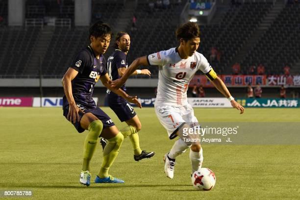 Ataru Esaka of Omiya Ardija controls the ball under pressure of Kazuhiko Chiba of Sanfrecce Hiroshima during the JLeague J1 match between Sanfrecce...