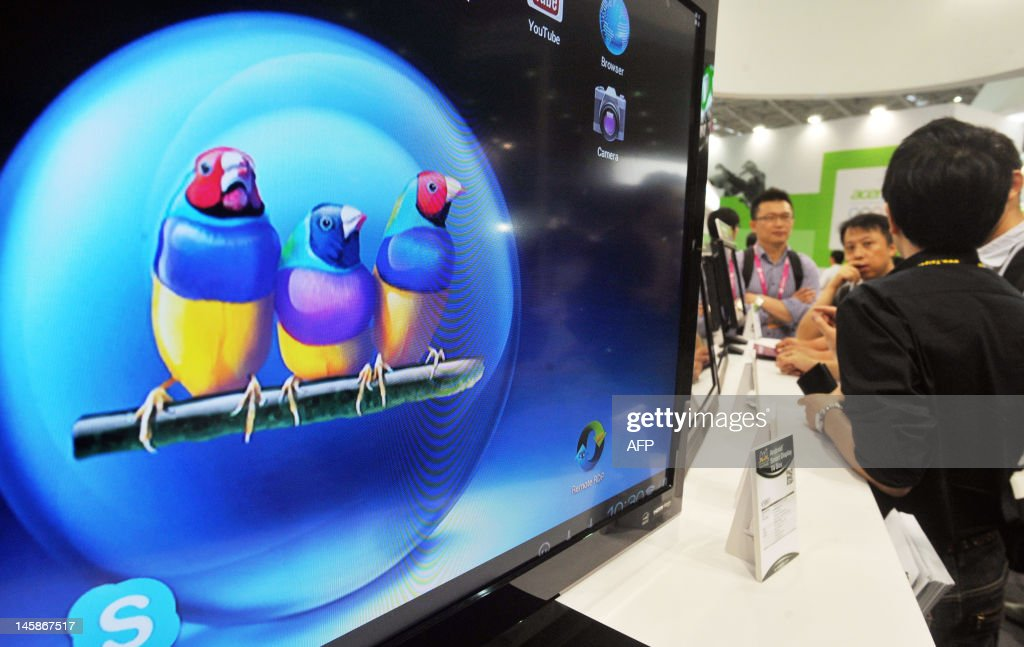 Ateendees look at the ViewSonic booth during the 2012 Computex in Taipei on June 7, 2012. Computex is Asia's leading IT trade fair. AFP PHOTO / Mandy CHENG