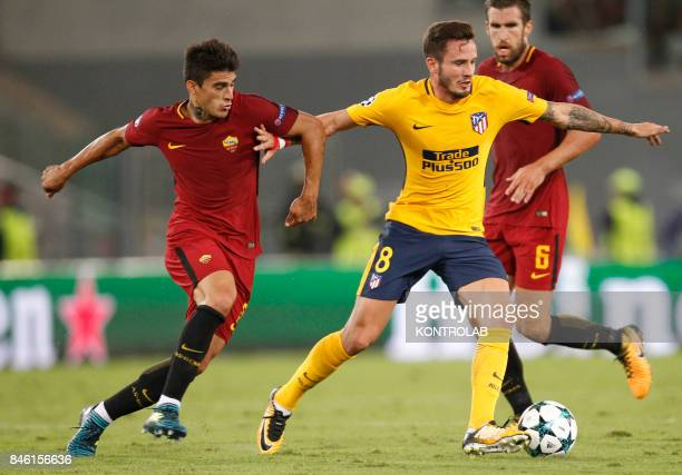 Ateletico Madrid's Spanish midfielder Saul fights for the ball with Roma's Argentinian midfielder Diego Perotti during the UEFA Champions League...