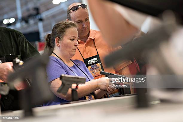 Atendees look over Glock Inc pistols on the exhibition floor of the 144th National Rifle Association Annual Meetings and Exhibits at the Music City...