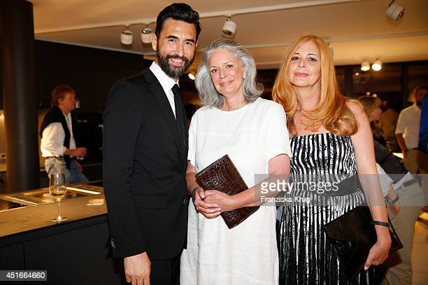 Athanasios Megarisiotis Christa Hoehs and Olivia Pascal attend the Bulthaup Showroom Opening on July 03 2014 in Munich Germany