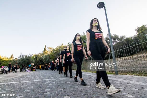 Athenians march silently wearing black outfit and yellow ribbons on their mouth during the 'Walk for Freedom' an antitrafficking protest taking place...