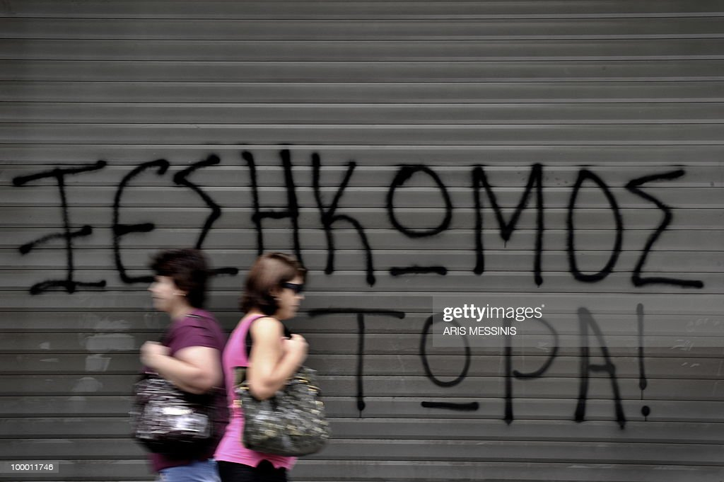 Athenians walk past a closed store painted with graffiti reading ' Uprising now ' during a protest marking the 24-hour gerneral strike against the austerity measures in central Athens on May 20, 2010. Thousands of protesters took to the streets of Athens and second city Thessaloniki in a new general strike against the government's debt-dictated austerity spending cuts and pension reform during a general strike.
