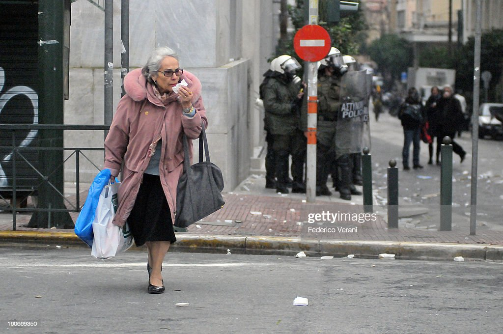 CONTENT] Athens 15 December 2010, A lady crossing the street during the clashes in the city centre