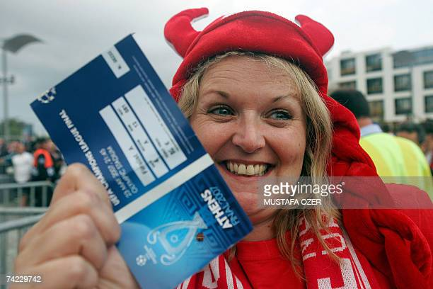 A football fan smiles as she shows her ticket to the Champions League football final match between Liverpool and AC Milan at the entrance of the...