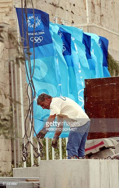 A worker hooks cables to a concrete block at the Panathinaiko stadium 08 August 2004 where will be held the Archery olympic competition and the start...