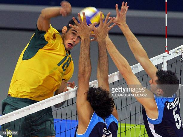 Brazil Dante Guimaraes Amaral spikes against Italian Valerio Vermiglio and Andrea Giani during preliminary pool B match of 2004 Olympic Games...
