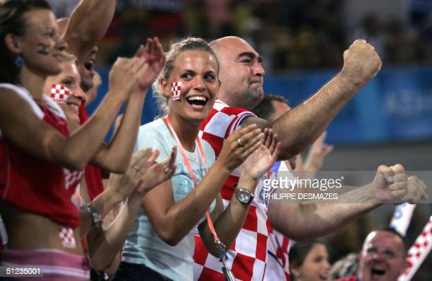 Croatian fans celebrate following their team's Olympic Games victory over Germany in the gold medal handball final at the Sports Pavillion 29 August...
