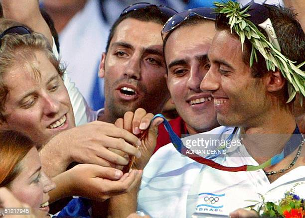 Gal Fridman of Israel is surrounded by supporters wanting to hold his gold medal during the medal ceremony after he won the Men's Windsurfer Mistral...
