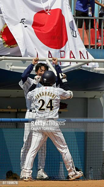 Japanese centerfielder Yoshinobu Takahashi celebrates with a teammate after he rounds the bases after hitting a homerun driving in pushing two other...