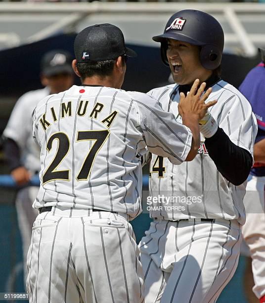 Japanese centerfielder Yoshinobu Takahashi celebrates with Tajura Kimura after hitting a homerun driving in pushing two other runs and tieing the...