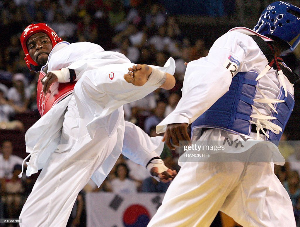 Pascal Gentil of France (L) fights against Chika Chukwumerije of Nigeria (R) during their men's under 80kg round of 16 taekwondo match at the Olympic Games in Athens, 29 August 2004. Gentil won the match. AFP PHOTO / Franck FIFE