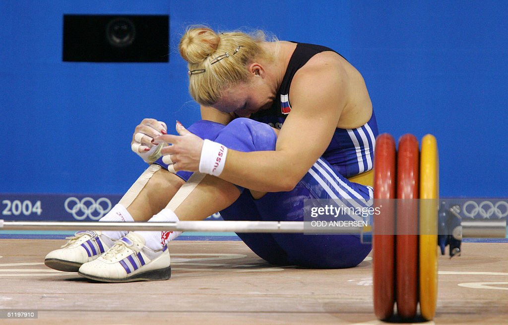Russian weightlifter and bronze winner Valentina Popova reacts to failing on her attempt to lift 150 kg in the clean jerk of the women's 75 kg...