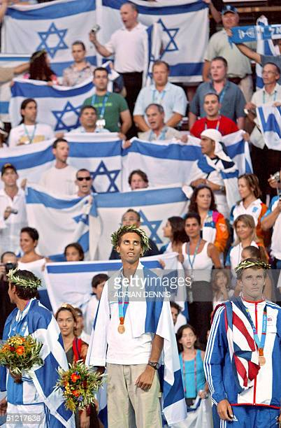 Surrounded by Israeli supporters Gal Fridman of Israel looks up as his flag is raised after he received his gold medal for winning the Men's...