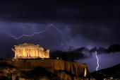 The ancient Greek Parthenon temple atop the Acropolis hill overlooking Athens is framed by lightning bolts during a thunderstorm that broke out in...