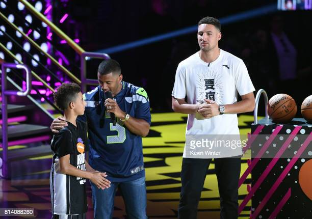 Athlete Austin Fernandes Cog Hill host Russell Wilson and NBA player Klay Thompson participate in a competition onstage during Nickelodeon Kids'...