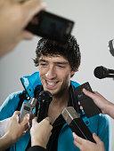 Athlete being interviewed by journalists, studio shot