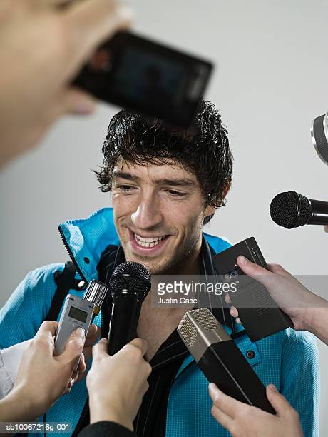 Athlete being interviewed by journalists, studio shot