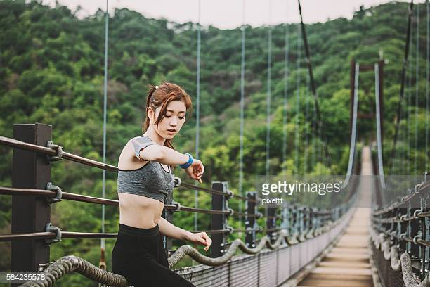 Athlete checking her smart watch in the mountain