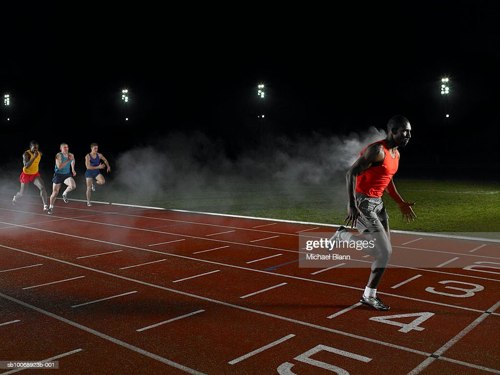 Athlete crossing finishing line with smoke trailing from behind