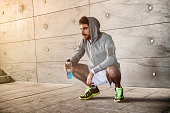 Athlete crouched with a sport drink