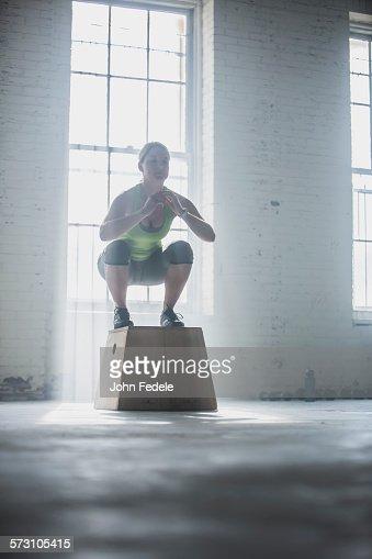 Athlete crouching on platform in gym