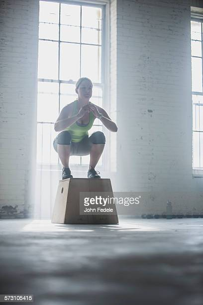 Athlete crouching on platform in gym