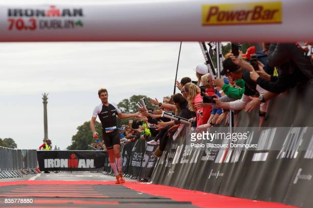 Athlete David McNamee from Great Britain celebrates winning the men's race of IRONMAN 703 Dublin triathlon at the finish line on August 20 2017 in...