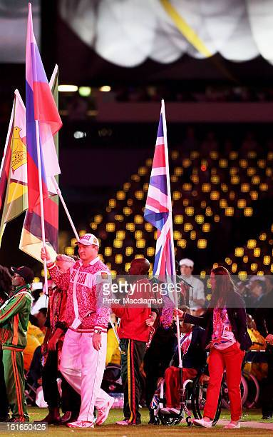 Athlete David Weir and cyclist Sarah Storey of Great Britain carry the flag join fellow flagbearers including athlete Alexey Ashapatov of Russia...