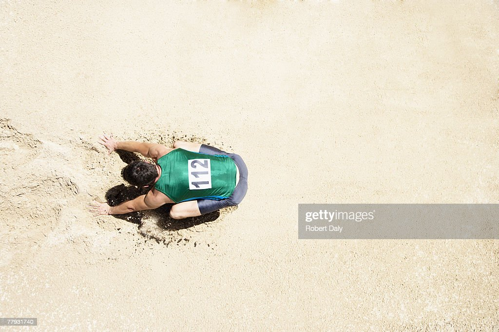 Athlete doing a long jump into a sandpit : Stock Photo