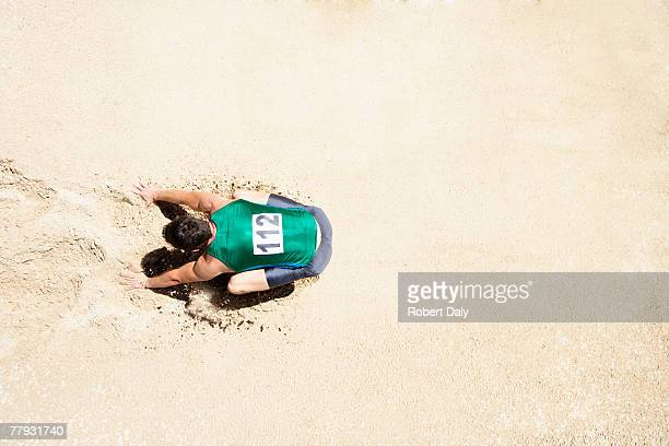 Athlete doing a long jump into a sandpit