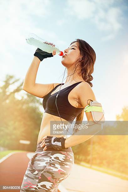 Athlete drinking energy drink after morning jogging on sunny day