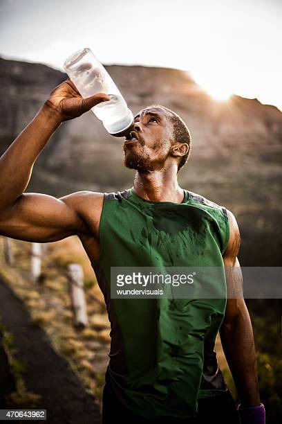 Athlete drinking thirstily from a water bottle outdoors