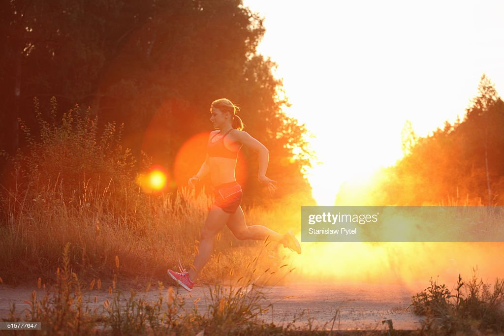 Athlete during training run in forest, sunset : Stock Photo