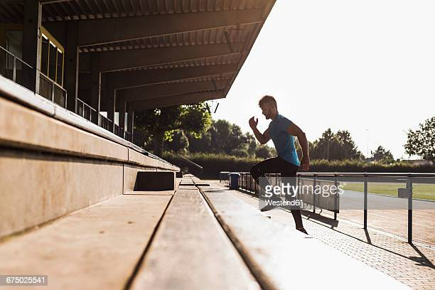 Athlete exercising on grandstand of a track and field stadium