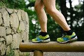 Mid adult man exercising outdoors, walking on balance beam.
