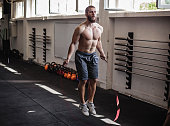 Muscular young man exercising with jumping rope