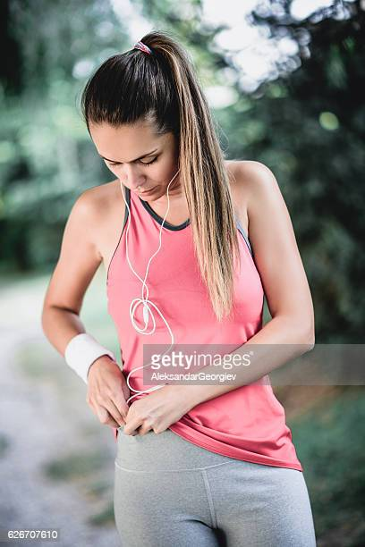 Athlete Female Preparing Music on Smartphone before Exercise in Nature