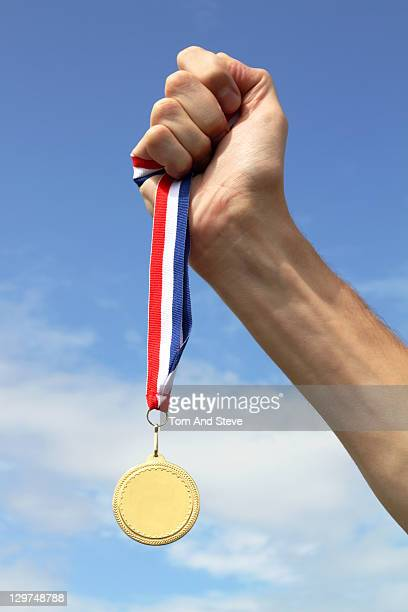 Olympic Athlete holding Gold Medal to the sky