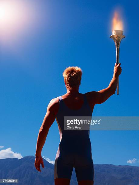 Athlete holding torch in scenic location