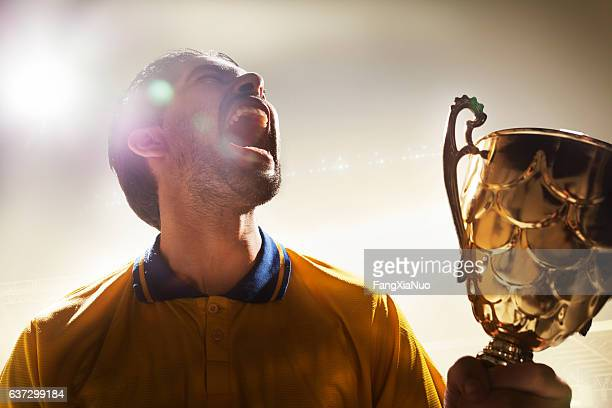 Athlete holding trophy cup in stadium