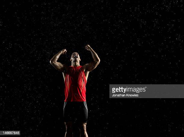Athlete in rain with arms raised in victory