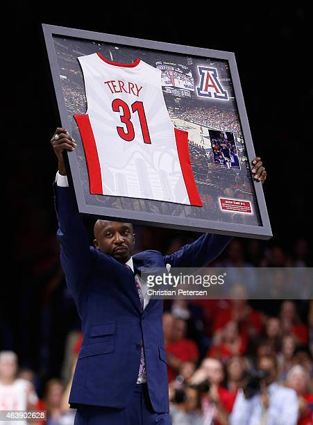NBA athlete Jason Terry of the Houston Rockets holds up a framed jersey as his number is retired by the Arizona Wildcats during a halftime ceremony...