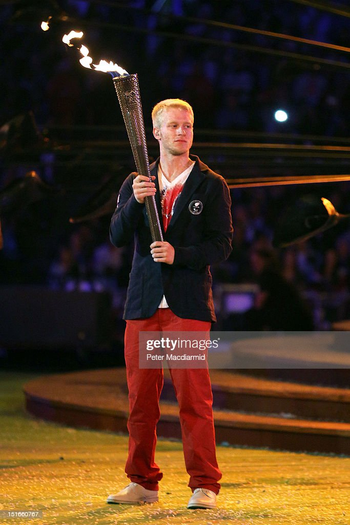 Athlete Jonnie Peacock lights a torch from the flame of the Paralympic cauldron as it is extinguished during the closing ceremony on day 11 of the London 2012 Paralympic Games at Olympic Stadium on September 9, 2012 in London, England.