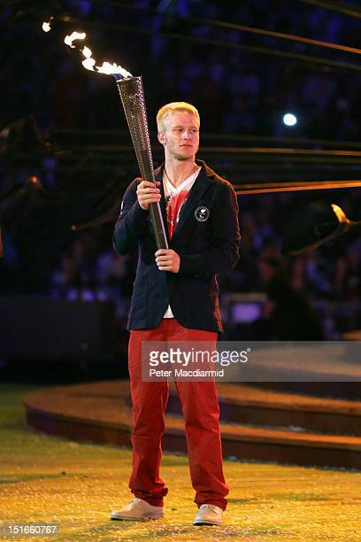 Athlete Jonnie Peacock lights a torch from the flame of the Paralympic cauldron as it is extinguished during the closing ceremony on day 11 of the...