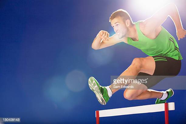 Athlete jumping hurdles