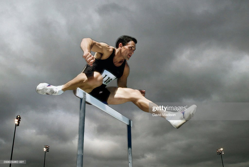 Athlete jumping over hurdle, low angle view : Stock Photo